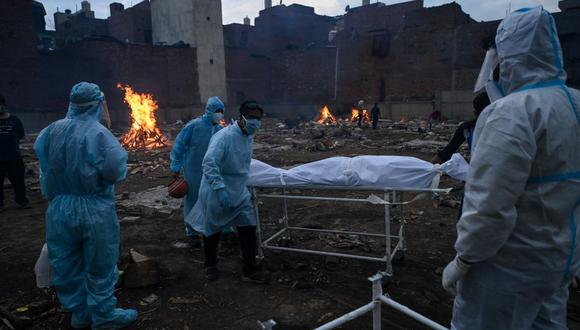 Relatives in personal protective equipment (PPE) suits carry the body of a person who died due to the Covid-19 coronavirus, at a cremation ground in New Delhi on May 6, 2021. (Photo by Prakash SINGH / AFP)