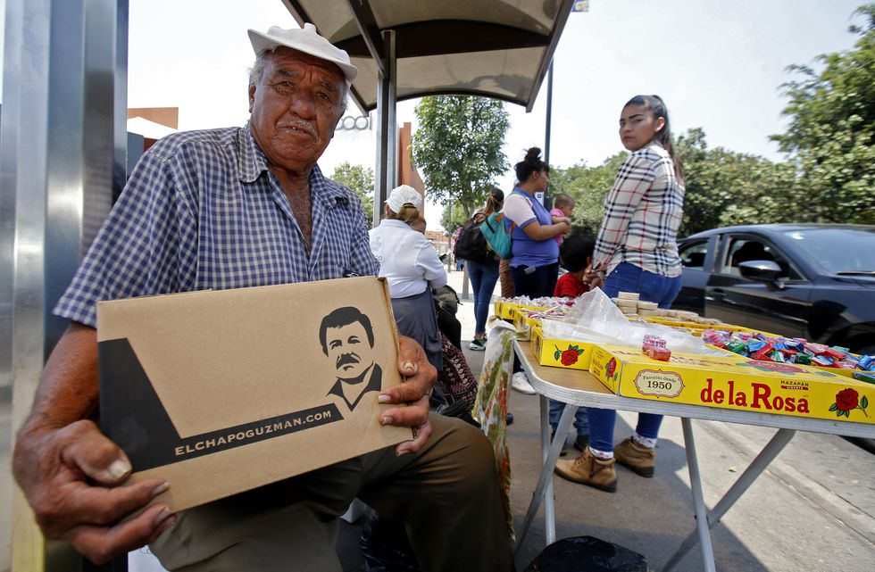 """A man poses with a box with donations of basic goods handed to him by employees of the foundation of Alejandrina Guzman, daughter of Mexican drug lord Joaquin """"El Chapo"""" Guzman, amid the new coronavirus pandemic in Guadalajara, Mexico, on April 17, 2020. (Photo by Ulises Ruiz / AFP)"""