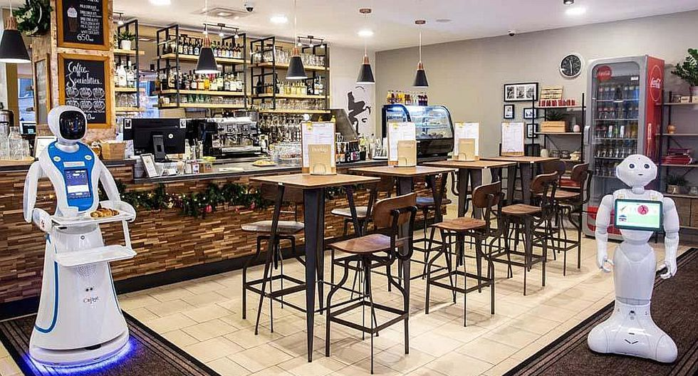 Androides sirven comidas y bebidas en un bar que muestra el futuro