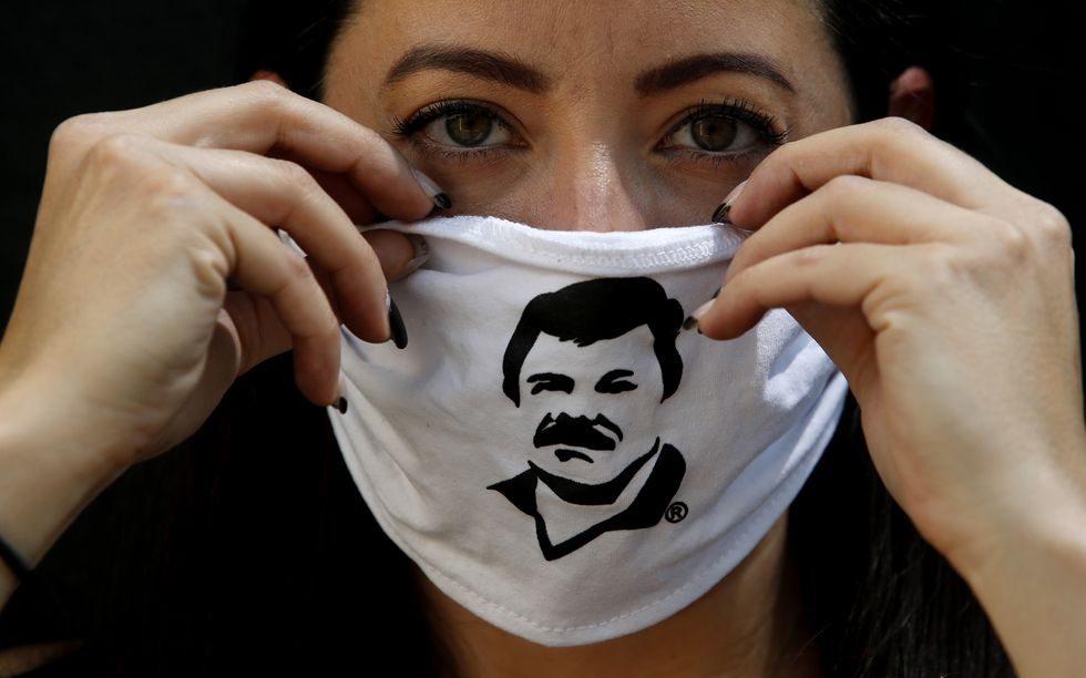 """An employee of the Alejandrina Guzman Foundation wears a face mask with the image of Mexican drug lord Joaquin """"El Chapo"""" Guzman -Alejandrina's father- as boxes with basic goods are filled to be donated to people in need amid the new coronavirus pandemic in Guadalajara, Mexico, on April 17, 2020. (Photo by Ulises Ruiz / AFP)"""