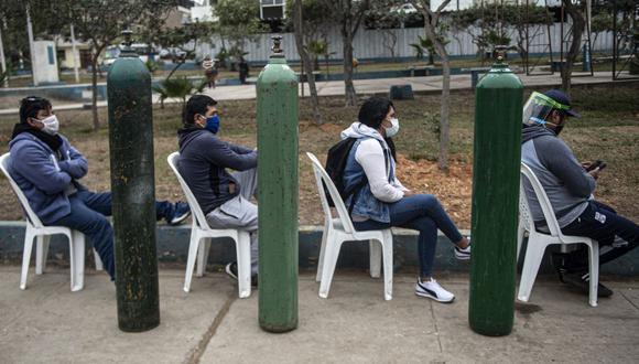 En la imagen, un grupo de personas hace fila para recargar tanques de oxígeno para pacientes graves de Covid-19. (Foto: Ernesto BENAVIDES / AFP).