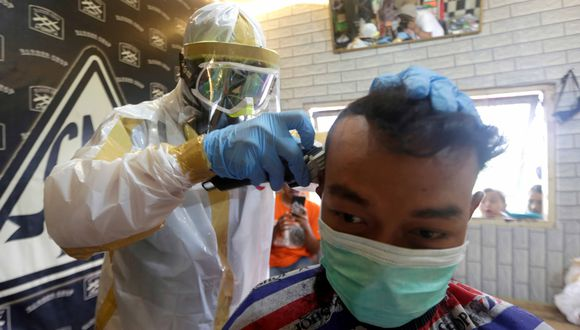 Bogor (Indonesia), 06/04/2020.- Barber Herman Mulyana (L) gives a haircut to a customer while wearing protective attire made from plastic garbage bags at a barbershop in Bogor, Indonesia, 06 April 2020. The Trade Ministry of Indonesia issued a regulation temporarily recinding all requirements for the import of protective gear and medical equipment, to counter shortages of many items used to treat COVID-19 patients and prevent the further spread of the disease. EFE/EPA/ADI WEDA