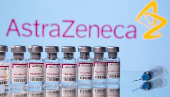 """Vials labelled """"Astra Zeneca COVID-19 Coronavirus Vaccine"""" and a syringe are seen in front of a displayed AstraZeneca logo, in this illustration photo taken March 14, 2021. REUTERS/Dado Ruvic/Illustration"""