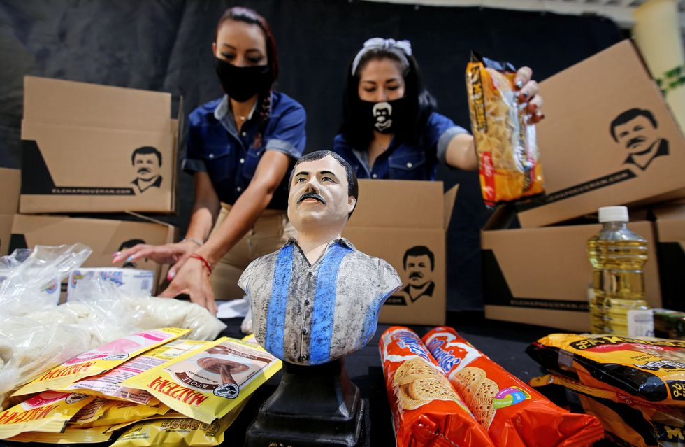 """Employees of the Alejandrina Guzman Foundation, one wearing a face mask with the image of Mexican drug lord Joaquin """"El Chapo"""" Guzman -Alejandrina's father-, arrange boxes with basic goods to be donated to people in need amid the new coronavirus pandemic in Guadalajara, Mexico, on April 17, 2020. (Photo by Ulises Ruiz / AFP)"""