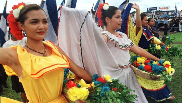 Estudiantes vestidas con trajes típicos de las cinco naciones centroamericanas llevan canastos de flores en el Estadio Nacional de Managua para conmemorar la Independencia de Centroamérica. Imagen del 14 de septiembre de 1999 (Foto: Miguel Álvarez / AFP)