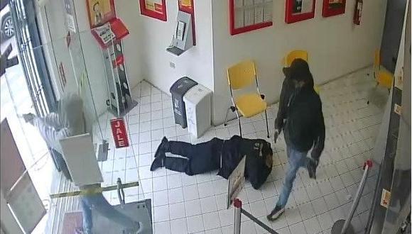 Uno de los delincuentes encapuchados en pleno asalto a la agencia bancaria que fue captado por las cámaras del recinto. (Captura de video)