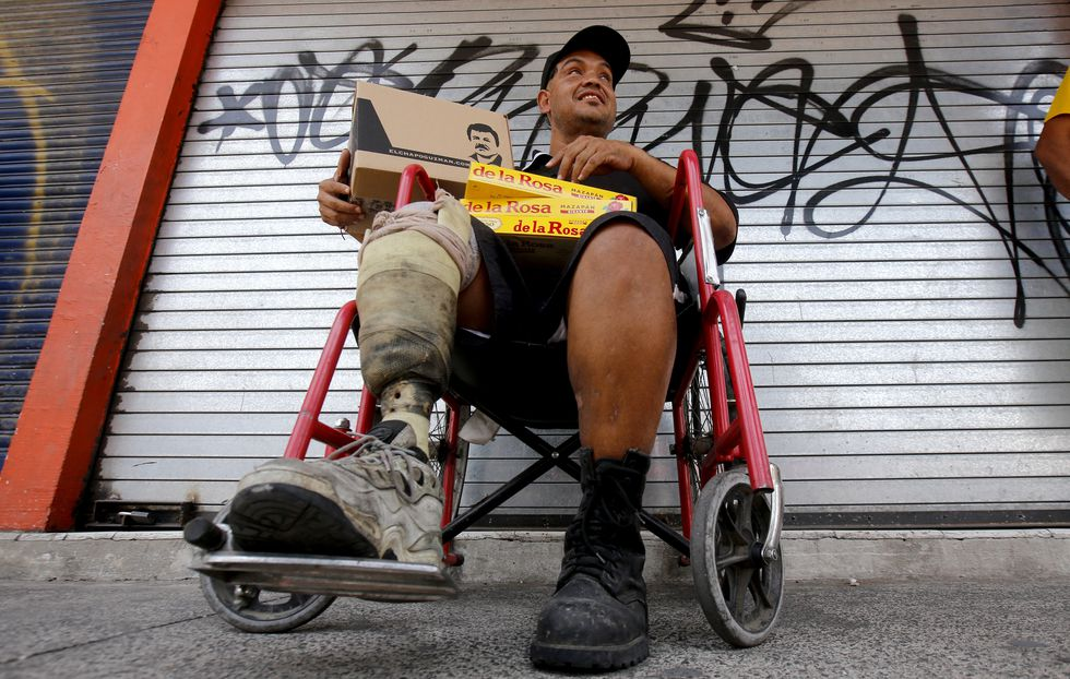"""A man in a wheelchair poses with a box with donations of basic goods handed to him by employees of the foundation of Alejandrina Guzman, daughter of Mexican drug lord Joaquin """"El Chapo"""" Guzman, amid the new coronavirus pandemic in Guadalajara, Mexico, on April 17, 2020. (Photo by Ulises Ruiz / AFP)"""