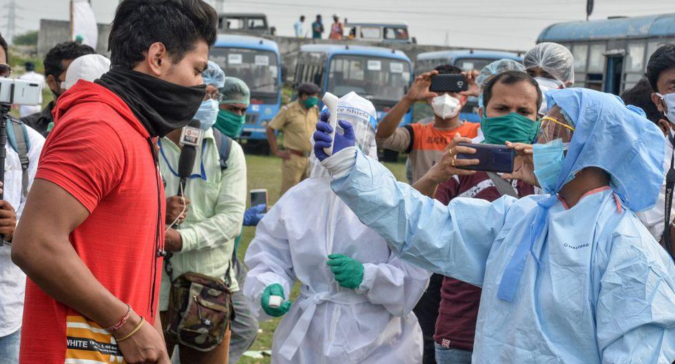 Un trabajador de salud verifica la temperatura corporal de un estudiante después de que llegó con otros en autobús desde otro estado a su hogar en el estado de Bengala Occidental durante un bloqueo nacional impuesto por el gobierno como medida preventiva contra el coronavirus (COVID-19). (DIPTENDU DUTTA / AFP)