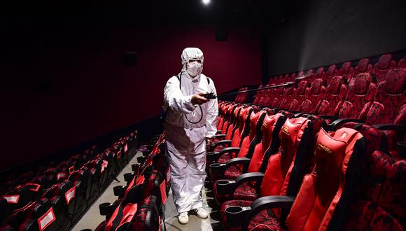 This photo taken on March 25, 2020 shows a staff member spraying disinfectant at a cinema as it prepares to reopen to the public after closing due to the COVID-19 coronavirus, in Shenyang in China's northeastern Liaoning province. - China lifted tough restrictions on the province at the epicentre of the coronavirus outbreak on March 25 after a months-long lockdown as the country reported no new domestic cases. (Photo by STR / AFP) / China OUT