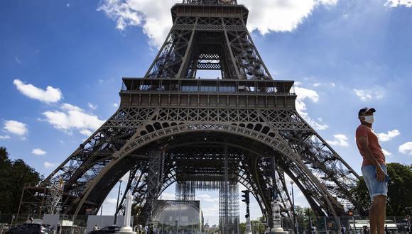 Un hombre con una máscara protectora camina cerca de la Torre Eiffel, en París, Francia, el 27 de agosto de 2020. (EFE/EPA/IAN LANGSDON).