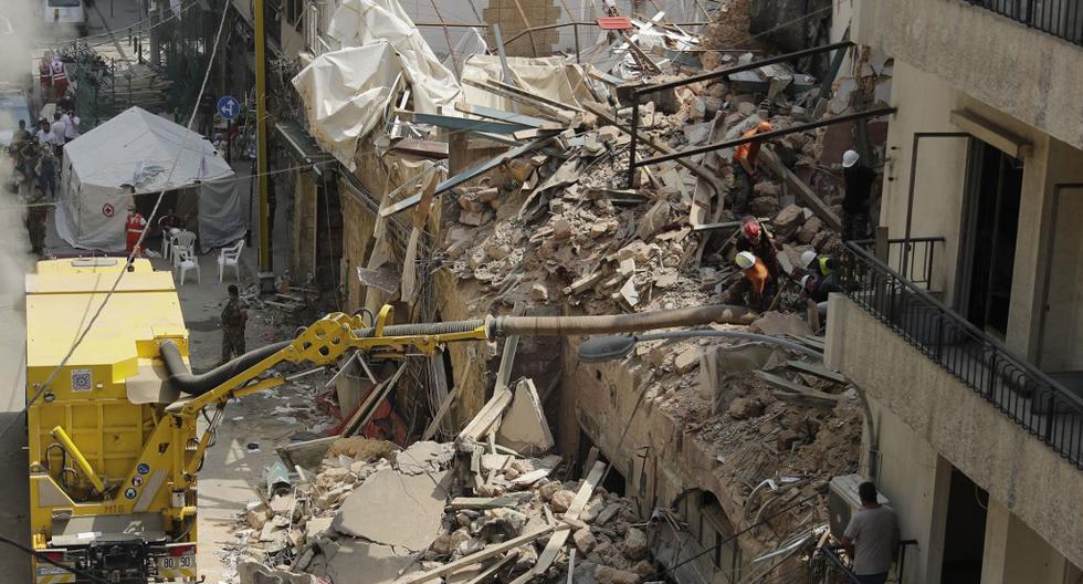 Los equipos de rescate se preparan para usar un tubo para aspirar los escombros de un edificio gravemente dañado en Beirut, la capital del Líbano, en busca de posibles sobrevivientes. (JOSEPH EID / AFP)