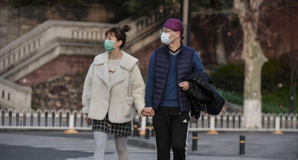 Esta foto muestra a dos personas caminando por una calle en Wuhan y usando mascarillas como medida preventiva contra el coronavirus COVID-19. China reportó solo ocho casos del brote de coronavirus COVID-19, sin nuevas infecciones domésticas fuera del epicentro de la provincia de Hubei. (AFP)