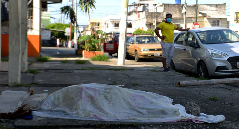 A man looks at a body said to be laying for three days oustide a clinic in Guayaquil, Ecuador on April 3, 2020. - Troops and police in Ecuador have collected at least 150 bodies from streets and homes in the country's most populous city Guayaquil amid warnings that as many as 3,500 people could die of the COVID-19 coronavirus in the city and surrounding province in the coming months. (Photo by Str / Marcos Pin / AFP)