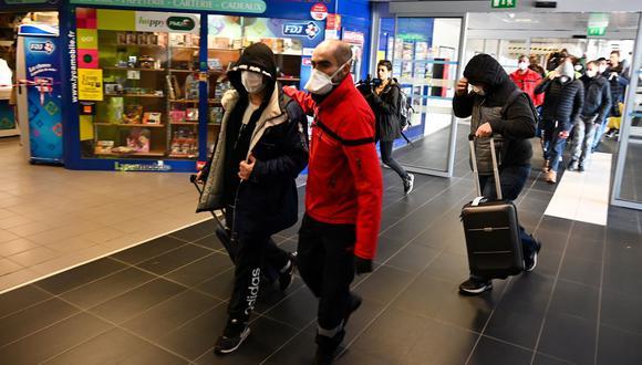 Un grupo de personas usan mascarillas protectoras son evacuadas de una estación de trenes y autobuses en Lyon debido a la sospecha de COVID-19. (AFP)