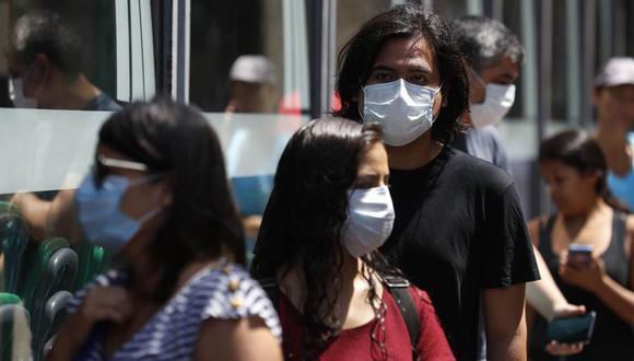 Personas con mascarillas en las calles de Lima. (Foto: EFE)